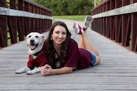 Lindsay and guide dog Quigley dressed in Aggie maroon while posing on a bridge.