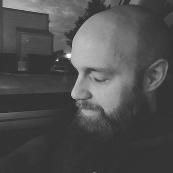 Justin shown in a black & white side portrait.