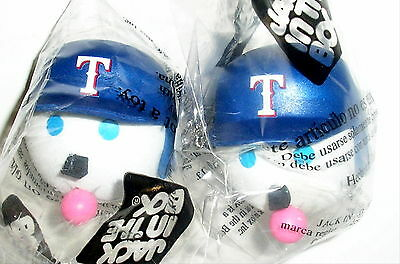 A Jack in the Box antenna topper blows a bubble gum bubble while wearing a Texas Rangers baseball cap.